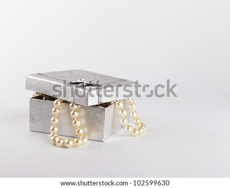 silver gift box with string of pearls on white background