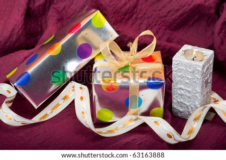 Silver gift boxes with colorful dots and ribbons and candle on burgundy background