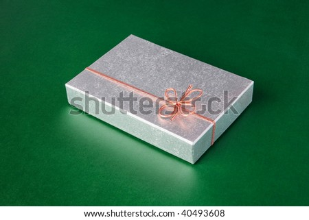 Silver gift package with red ribbon on green background