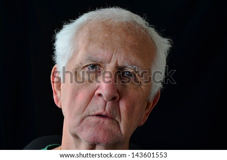 Silver-gray hair and grizzled beard of old man with sad eyes against black background create dark, remorseful image.