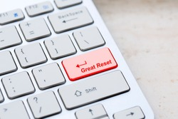 Silver grey keyboard close up with world global great reset enter- button on marble background.