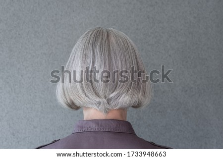 Silver-haired mature lady on gray background, from behind. ストックフォト ©