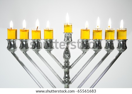 Silver Hanukkah candles with oil candles, all candles lite on the traditional Hanukkah menorah
