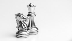 Silver horse and queen chess standing on white background. - Business winner and fight concept.