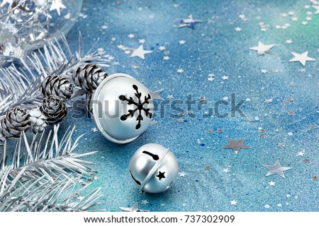 silver jingle bells with christmas tree branches and decoration on blue background closeup view