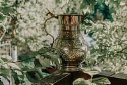 Silver jug. Ancient traditional silver jug and vintage silver bottle in nature background.