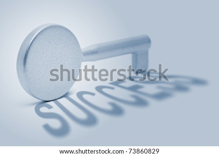 Silver key with shadow that spells success