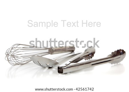 Silver kitchen utensils including whisk, tong and spoon on a white background with copy space