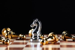 Silver knight chess defeats gold pawns on wooden chessboard. Intellectual duel and tactical battle in business. Strategy planning, leadership and teamwork. Checkmate and winning in game concept.