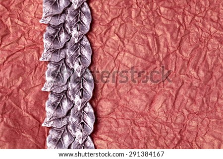 silver leaves ornament on gold crumpled tissue paper texture for background