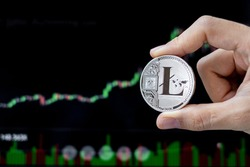 Silver Litecoin (LTC) cryptocurrency coin with candle graph background, Crypto is Digital Money within the blockchain network, is using technology and online internet exchange.
