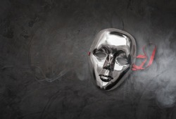 Silver mask in the dark background.Deception concept Conceal.The concept of lying and concealing reality.Halloween concept.
