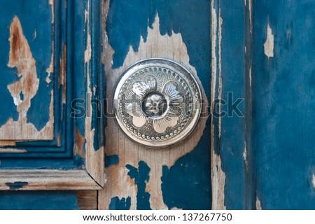 Silver metal door knob on an old wooden door