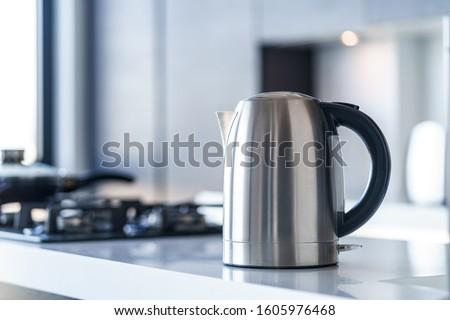 Silver metal electric kettle for boiling water and making tea on a table in the kitchen interior. Household kitchen appliances for makes hot drinks Stock photo ©