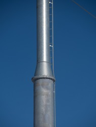 silver metal industrial pole for chair lift at ski lift on blue sky day in winter