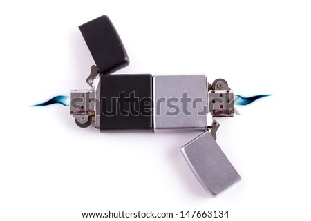 Silver metal lighters on white background with blue flame.