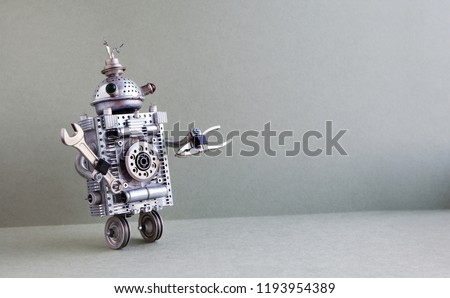 Silver metallic robot handyman on gray background. Two wheels domestic servant robotic character with hand wrench plier tools. Creative design steampunk toy, copy space.