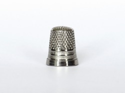 Silver metallic thimble front view for needlework isolated on white background.