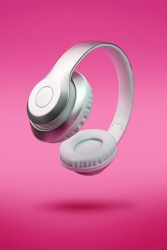 Silver metallic white wireless headphones in the air on neon pink magenta background. Trendy minimal luxury music portable device magic flying levitation concept. New technologies. Close up macro