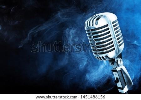 Silver microphone closeup on blue smoke background #1451486156