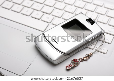 Silver mobile phone on a white laptop. Top view. Selective focus on a phone. No dust and scratches! Studio shot. ISO 100.