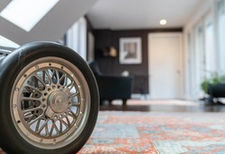 Silver model roadster. Vintage toy chrome pedal race car. Wheel and steering wheel are clean on a shiny toy car indoors on a red carpet.