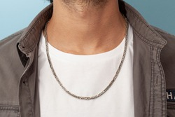 silver necklace on man's neck wearing gray shirt and white t-shirt
