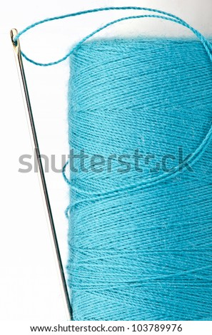 silver needle with golden head thrusted in a part of blue thread