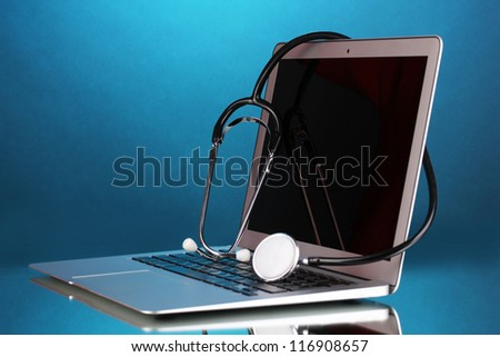 Silver notebook with a stethoscope on blue background with reflection - stock photo