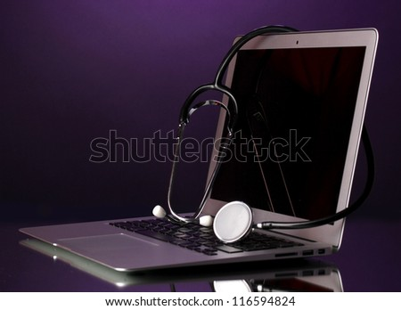 Silver notebook with a stethoscope on purple background with reflection