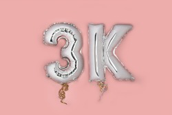 Silver Number Balloons 3K, meaning three thousand, on pink background. Holiday Party Decoration, 3k followers or likes, social media or postcard concept with top view