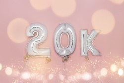 Silver Number Balloons 20K, meaning twenty thousand, on pink background. Holiday Party Decoration, 20k followers or likes, social media or postcard concept with top view