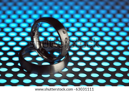 silver or titanium wedding rings on perforated sheet metal in blue light