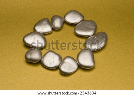 Silver painted stones set against a gold background.