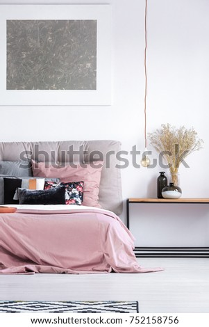 Silver painting above king-size bed with gray headboard and pink bedding in cozy interior of modern bedroom  #752158756