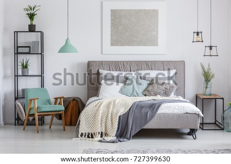 Silver painting above king-size bed with knit beige blanket in adorable bedroom with mint retro chair #727399630
