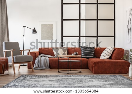 Silver painting on white wall of elegant living room interior with brown corner sofa with pillows #1303654384