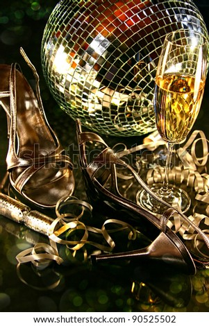 Silver party shoes on floor with champagne glass for New Year's Eve - stock photo