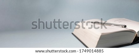 silver pen lying on an opened white empty thick book on gray blue background. banner with copy space. reading learning studying concept ストックフォト ©