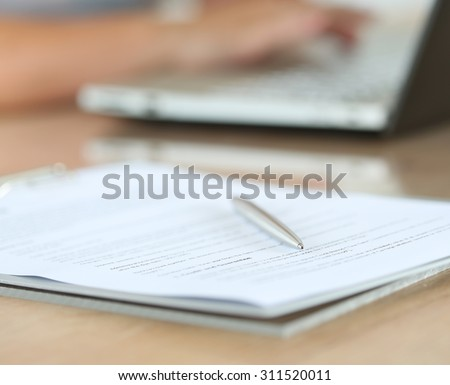 Silver pen lying on document pad while female hands working on notebook pc in background. Office life, paperwork, client contract, business agreement concept. Focus on pen