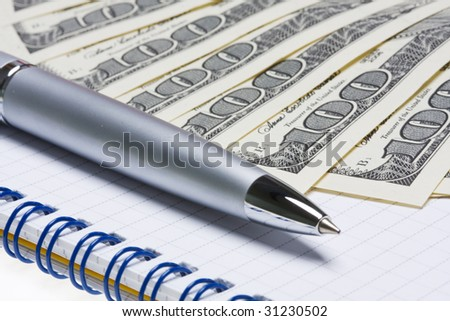 silver pen on the background of the dollar banknotes - stock photo
