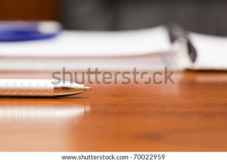 Silver pen on the table near a notebook