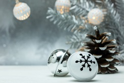 silver pine cone and christmas jingle bells on gray blurred background with fir tree branch and garland lights