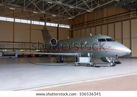 Silver private jet with two engines in hangar
