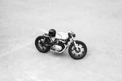 Silver rebuilt motorcycle motorbike cafe-racer is parked alone. Wild lifestyle. View from above