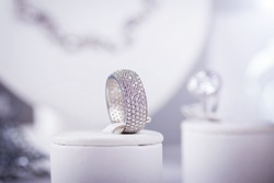 Silver ring with little diamonds. Isolated on grey. Lens flare. Small depth of field