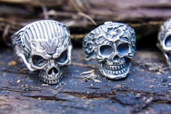 Silver rings skulls closeup in full face on a dark wooden surface. Jewelry in biker and rocker style