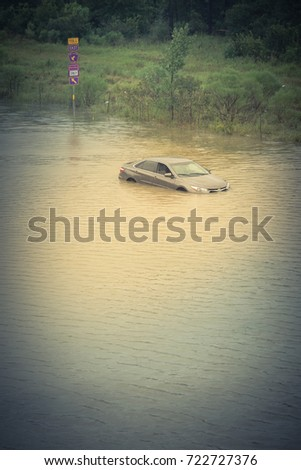 Silver sedan car swamped by flood water in East Houston, Texas, US by Harvey Storm. Submerged car on deep heavy high water road. Disaster Motor Vehicle Insurance Claim, severe weather. Vintage tone #722727376