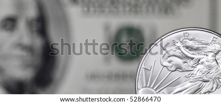 Silver shiny dollar coin on a background of blurry one hundred dollar bill