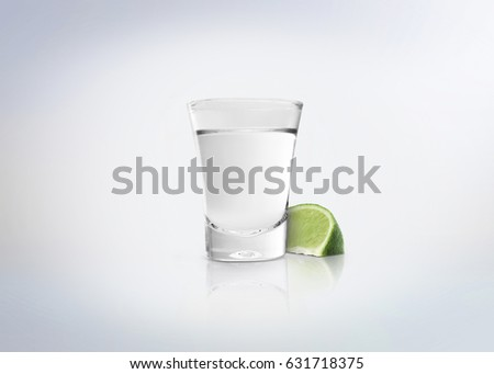Silver shot of tequila. Alcoholic distilled beverage with slice of lemon / lime on the side. Isolated on white background.